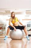 Sittinig rubio de la muchacha en la bola de plata en gimnasia de la aptitud Imagen de archivo