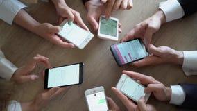Sittinng de Businessworkers en un círculo y trabajo en sus smartphones junto almacen de metraje de vídeo