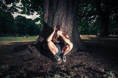 Sittng depresso della donna sotto un albero Immagini Stock Libere da Diritti