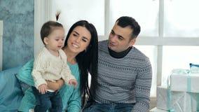 Sittng felice della famiglia sul davanzale decorato con gli accessori di Natale archivi video