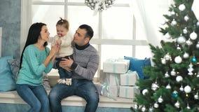Sittng felice della famiglia sul davanzale decorato con gli accessori di Natale stock footage