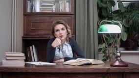 Sittnig di pensiero della donna seria allo scrittorio del lavoro con i libri Immagine Stock