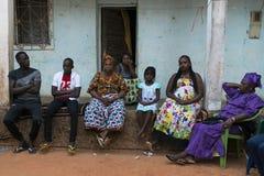 sittting在他们的房子前面的家庭在Cupelon de Cima邻里在市比绍,几内亚比绍 库存照片