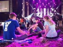Sittting hållande ögonen på musik för folkmassa på festivalen Arkivbilder