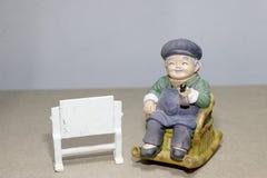Situação bonita da boneca da avó que balança a cadeira de bambu no fundo de madeira - ainda vida Imagem de Stock Royalty Free