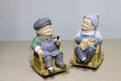 Situação bonita da boneca da avó que balança a cadeira de bambu no fundo de madeira - ainda vida Imagem de Stock