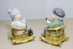 Situação bonita da boneca da avó que balança a cadeira de bambu no fundo de madeira - ainda vida Imagens de Stock Royalty Free