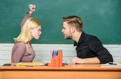 Situação do conflito O professor e o professor primário estão na discussão Mulher irritada que vai equipar com seus punhos Pares  fotografia de stock royalty free