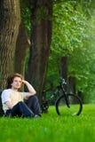 Situação do homem novo sob a árvore perto de seu bycicle Imagens de Stock Royalty Free