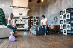 Situação do pai e da mãe no sofá que joga balões de ar com os dois filhos pequenos Fotografia de Stock Royalty Free