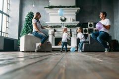 Situação do pai e da mãe no sofá que joga balões de ar com os dois filhos pequenos Imagens de Stock Royalty Free