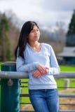 Situación adolescente joven de la muchacha, inclinándose contra la verja en el parque Imagenes de archivo