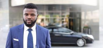 Situación africana joven del hombre de negocios cerca del edificio de oficinas y mirada de la cámara fotos de archivo