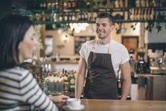 Situación alegre del barista en el contador y la sonrisa de la barra fotos de archivo libres de regalías