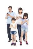Situación asiática de la familia y usar el teléfono elegante junto Fotografía de archivo libre de regalías