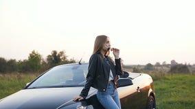 Situación atractiva de la mujer joven cerca del cabriolé almacen de metraje de vídeo