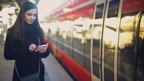 Situación atractiva de la señora cerca del tren y el mecanografiar en el smartphone, boletos en línea almacen de video