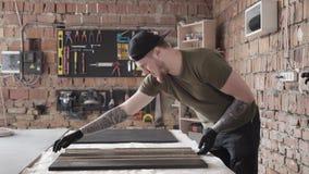 Situación barbuda del funcionamiento del craftman de la habilidad en la tabla en garaje Un hombre trabaja en un taller El tablero almacen de metraje de vídeo