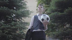 Situación bien vestida hermosa del muchacho en la calle que sostiene la bola y el monedero de fútbol Hombre joven serio simultáne almacen de metraje de vídeo