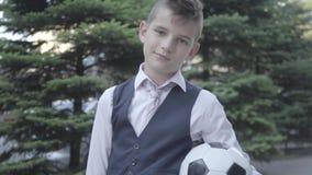 Situación bien vestida linda del muchacho del retrato en la calle que sostiene la bola y el monedero de fútbol Hombre joven serio metrajes