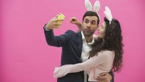 Situación blanda joven de los pares en un fondo rosado Mirada del teléfono mientras que hace el selfie en el teléfono móvil con