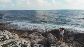 Situación caucásica de la mujer en los acantilados con el teléfono celular de la cámara que toma las fotos del horizonte de mar c