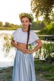 Situación caucásica hermosa joven de la mujer en el banco del río Imagen tradicional del campo con la muchacha en el primero plan foto de archivo libre de regalías