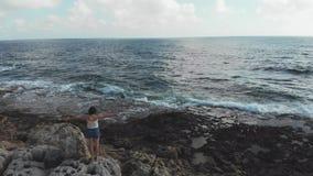 Situación caucásica joven de la mujer en roca grande con el mar tempestuoso de mirada abierto de par en par del océano de los bra