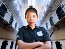 Situación china asiática seria y atractiva joven de la mujer del guardia en el uniforme de la policía del pasillo de la prisión d fotos de archivo
