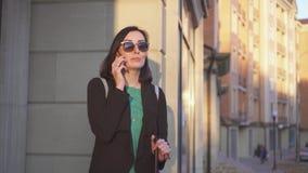 Situación ciega de la mujer en la calle con un bastón en su mano y el hablar en el teléfono almacen de metraje de vídeo