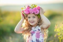 Situación de 3-4 años sonriente del bebé con la cesta de flores al aire libre mirada de la cámara Estación de verano foto de archivo