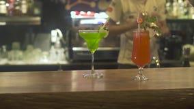 Situación de adornamiento de las frutas del cóctel alcohólico en contador de la barra en pub Camarero que hace la ensalada de fru almacen de metraje de vídeo