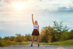 Situación de la chica joven en el camino con su mano para arriba, el concepto de éxito fotografía de archivo libre de regalías
