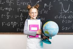 Situación de la colegiala de la muchacha en la pizarra y los cuadernos el sostenerse foto de archivo libre de regalías