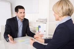Situación de la entrevista o de la reunión de trabajo: hombre y mujer de negocios en el de Imagenes de archivo