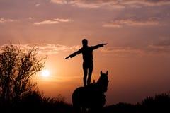 Situación de la muchacha en un caballo con las manos aumentadas al lado como un ala del aeroplano fotos de archivo libres de regalías