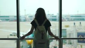 Situación de la muchacha en la ventana en el terminal de aeropuerto almacen de video