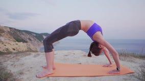 Situación de la muchacha de la yoga en una actitud del puente en un lugar hermoso en el verano por el océano en una montaña Mañan almacen de video