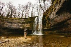 Situación de la mujer delante de una cascada que cae abajo una pared de piedra redondo formada r imágenes de archivo libres de regalías