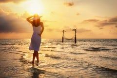 Situación de la mujer en una playa tropical y disfrutar de la puesta del sol imagenes de archivo