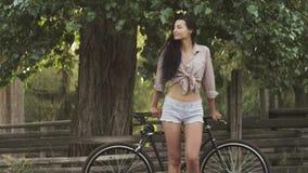 Situación de la mujer joven con una bicicleta al aire libre almacen de metraje de vídeo