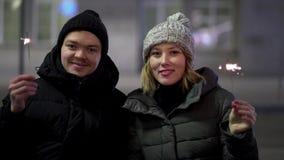 Situación de la mujer joven y del hombre exterior con las bengalas y la sonrisa, el concepto de la Feliz Navidad y del Año Nuevo  almacen de video
