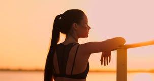 Situación de reclinación del rato de la mujer en la barra de la puesta del sol cerca de la vista posterior Una mujer morena hermo almacen de video