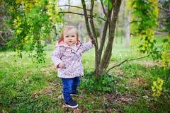 Situación de un año de la muchacha al lado de un árbol fotos de archivo libres de regalías