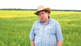 Situación del granjero en campo y hablar algo, sombrero de vaquero del desgaste en un día soleado almacen de metraje de vídeo
