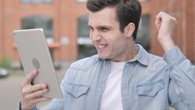 Situación del hombre al aire libre y que anima para el éxito en la tableta almacen de metraje de vídeo