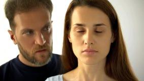 Situación del hombre detrás de la esposa, señora triste con los ojos cerrados que oye decisiones del marido foto de archivo