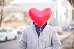Situación del hombre en la calle y la cara de ocultación detrás del balón de aire rojo formado como corazón Concepto del día de S imagenes de archivo