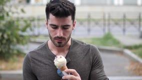 Situación del hombre joven, comiendo un helado sabroso almacen de metraje de vídeo