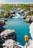 Situación del hombre joven en un aove de la roca una corriente azul que fluye adentro a un campo verde imagenes de archivo